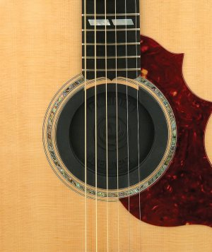 Acoustic guitar with a rubber soundhole cover